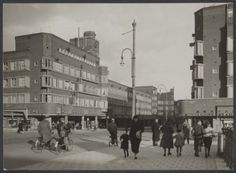 1950's. A view of the Mercatorplein and Jan Evertsenstraat in Amsterdam-West. The Mercatorplein borders the Hoofdweg at the junction with the Jan Evertsenstraat. The square was designed by H. P. Berlage in 1925 and built in the late 1920's. Remarkable were the two towers on the north and south-side of the square. The first part of the Jan Evertsenstraat is a busy shopping street, but beyond the Mercatorplein there are very few stores. #amsterdam #1950 #Mercatorplein #JanEvertsenstraat
