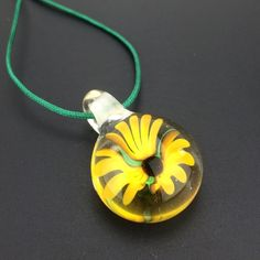 "Sunflower Pendant Blown Glass Lampwork Floral Bead The look of a preserved flower, a yellow-orange bloom with dark center and green foliage encased in a domed pendant. Made entirely of glass imported from Italy, I individually work the molten glass into these pendants via torch flame in my Tampa Bay studio. My glass goes from torch to kiln for a digitally controlled cool down overnight for a proper anneal. No matter how hard I try, no two exactly alike. Approx. 1.25"" long. Handmade USA. SRA…"