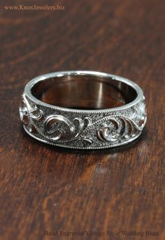 Crafted in 14k white gold, Juliet is a wider band with very intricate details. The hand engraved curls are done in a rare relief engraving style, and the hand stippled background creates the perfect contrast to highlights every curl. The domed band has a fine milgrain edge framing the center design. A unique vintage style wedding band for men and women.