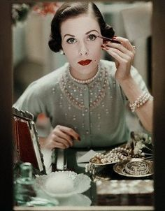 1940s lady at her dressing table applying makeup. Love all her pearls!