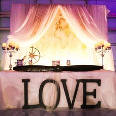 The aeronautical theme was incorporated into the reception decor with an airplane propeller adorning the sweetheart table in place of a more traditional swag. A world map served as the background for the table and was draped with light, airy fabric that gave the impression that the couple was sitting in the clouds.