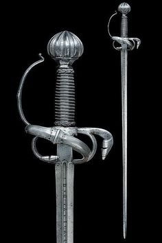 "A fine rapier Straight, double-edged blade of lenticular section, grooved at the first part signed ""TOMAS D'AIALA""; rectangular tang, elegant hilt with lower-side ring, chiselled with curls, outlined at the borders, deeply grooved pommel; wooden scabbard with iron wire binding and moor's heads. dating: third quarter of the 16th Century provenance: Southern Germany condition report: very good- by Czerny's International Auction House"