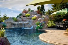 This lagoon swimming pool features a vanishing edge, rock waterfall, slide, beach entry with rock accents, water geysers and a large travertine patio