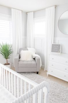 White and Grey Gender-Neutral Nursery, White and Gray Gender-Neutral Nursery with white drapes, soft gray feeding chair and gold accents