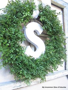 Boxwood Wreath embellished with wooden letter placed infront of old window frame.  My Uncommon Slice of Suburia