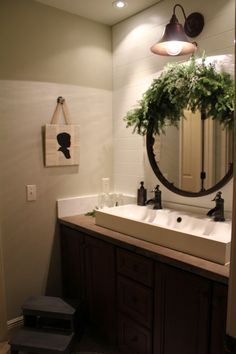 Even bathrooms can get in the holiday spirit!  We love this oversized old fashioned sconce above the sink-brings in the old world charm.  Trough sinks are gaining popularity, and for good reason, they look great!  It is accented by the old fashioned pump faucets by , it's one of our favorites!  Add a little evergreen around the mirror and you have a classic holiday bathroom.