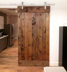 Interior Design Trend 2015 - Sliding Barn Doors! This #custom door provides an element of rustic charm and convenience to this homes interior space! #reclaimedwood provided by #TrueAmericanGrain! #slidingbarndoor #interiordesign #repurposedwood #recycledwood #barnwood #barndoor