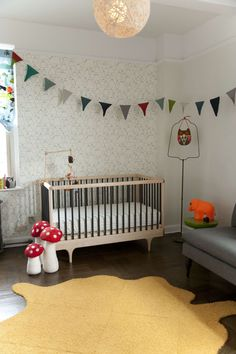 This hip nursery features trendy elements like triangle flag garland, whimsical plush crocheted accessories, and wallpaper with a hand-drawn feel. All this with an eco-friendly crib and a fist full of DIY projects makes this nursery truly personal and unique.