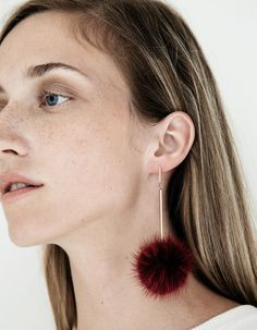 From Tuleste, a pair of mink fur pom pom earrings in Rose with rose gold-toned…