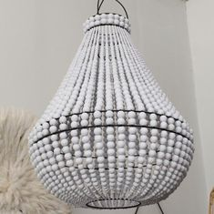 White wooden bead chandelier with matching white contrast band beading.  This chandelier comes with no electrical wiring. A qualified electrician must drop the