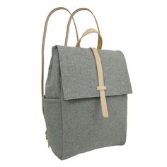 Kate Sheridan Grey Felt Bow Rucksack: The Bow Rucksack made in beautiful crisp grey wool felt with Italian leather straps is roomy enough to carry all your essentials about town. Featuring hidden magnetic fastenings and multiple pockets inside and out to keep super organised on the go.