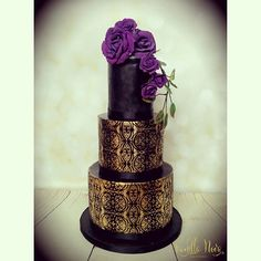 Black wedding cake with gold airbrushing and purple roses