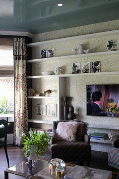If you're looking for a really stunning way to style a wall, think about creating shallow shelves that work for displaying the stuff you love while defining hung items. And it's an easy DIY that works when built around a floating TV or standalone piece of art. And placing a reflective wallpaper behind the display creates a really interesting space.