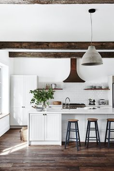 All white kitchen and dark wood beams. Industrial Barstools