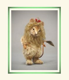 """Wizard of Oz™ Cowardly Lion - R. John Wright Dolls. The Cowardly Lion comes authentically outfitted in a full lion suit made of fine mohair with subtle airbrushed coloration and felt paw pads. His mohair curls cascade around his face and are topped with a tiny red silk bow. A tuft of fur at the tip of his mousey tail completes his trademark ensemble. Measuring just 3"""" tall, a built-in metal stand provides effortless display. #RJWDolls #RJohnWrightDolls #CollectibleDolls"""