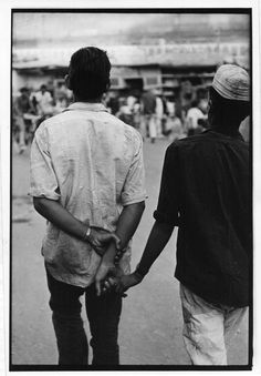 Two men walking down the street holding hands with their backs to the camera.. From Duke Digital Collections. Collection: William Gedney Photographs and Writings. Mark: None. Date of print: Unknown.