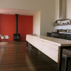 A multi-functional spaceis a kitchen designer's dream. And it's especially beneficial when trying to maximize resources insmalleror oddly shaped kitchen. In this long, narrow room, a kitchen counter pulls triple duty as an island, desk, and a grand table. The leaf raises to form a dining table for 12.