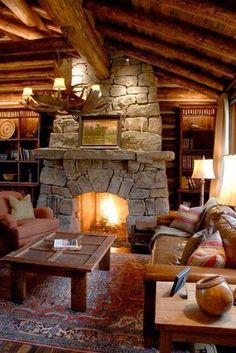 W salonie całą uwagę przykuwa do siebie kominek w całości zbudowany z kamienia. Meble oraz dodatki w kolorach ziemi podkreślają ciepły klimat wnętrza.