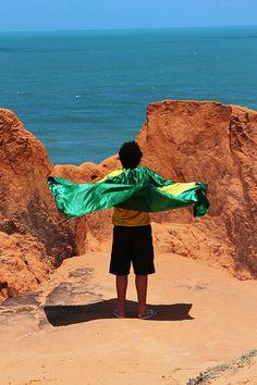 Jovem com bandeira do Brasil, no Labirinto das Falésias, Morro Branco, Ceará