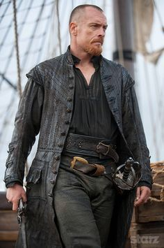 """Dewuchi"" Brings Toby Stephens Black Sails Captain Flint Black Leather Trench Coat for Men. Toby Stephens Worn This Fabulous Trench Coat in TV Series Black Sails as Captain Flint. Made from Real Leather Available at Our Online Store. Captain Flint, Long Leather Coat, Leather Trench Coat, Real Leather, Black Leather, Leather Jackets, Black Sails Season 2, Flint Black Sails, Toby Stephens"