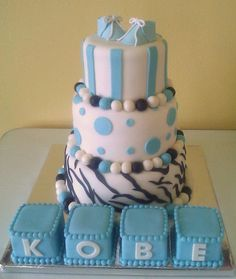 """A three tier fondant covered cake in blue, black and white, adorned with edible """"beads""""  and topped off with edible sugar paste baby shoes.  The baby blocks in front are sculpted from cake covered with fondant and embellished with edible """"beads"""" around the edges.  Created by Sweet Pea Cake Co in Colorado Springs"""