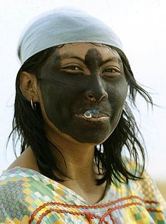 She blackened her face with a powder extracted from a root to protect it against sunburn. She smokes her cigarette holding the lighted side inside her mouth. People Around The World, Around The Worlds, Madonna, Tribal People, World Cultures, Tribal Art, First Nations, Wonders Of The World, South America