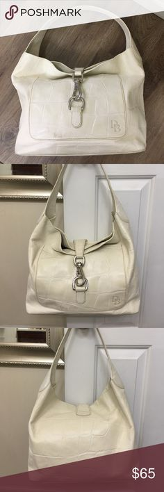 Dooney & Bourke Off White Croc Shoulder Bag 100% authentic Dooney & Bourke shoulder bag. The outside of the bag features a shiny nickel hook clamp closure, an outside front pocket, inside a beautiful red interior with an inside zipper and one compartment for your phone. The outside of the bag has normal wear from use. Minor marks and scuffs on the exterior. The interior is immaculate and looks almost new. Measurements are Dooney & Bourke Bags Shoulder Bags