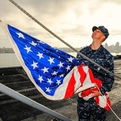 A Sailor prepares to hoist the national ensign before morning colors aboard the aircraft carrier USS Ronald Reagan. Morning colors are executed every morning at 0800. #Navy #USNavy #AmericasNavy navy.com