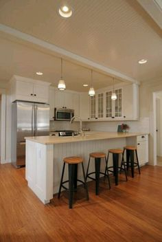 This is the kitchen for me! White cabinets, glass fronts, stools, wainscoting, white granite, handles, subway tile.