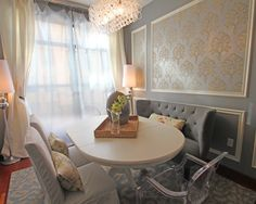 This is lovely, the color, the wall treatment, tufted banquette, the acrylic chair, the rug, & love the light fixture.