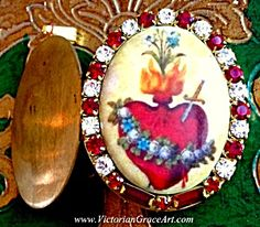 $79 Vintage Red Rhinestone Locket Sacred Heart Milagros (Image1)Religious pendant with a porcelain cameo featuring the Flaming Sacred Heart with a flower garland. Deep ruby red and clear rhinestones surround. The vintage locket is brass and copper; may hold 2 photo's or your personal prayer petition.