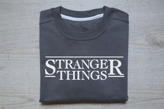 Handprinted adult sweatshirt in vintage heather dark gray color with Stranger things in white designed and printed by wear2.me. Sweater is printed in silk screen printing technique with water-based Eco friendly ink.  Adult sweatshirt very soft and is really comfortable to wear and has soft thin fleece inner. Sweater is classic-fitted with twin-needle topstitch at neck and shoulder and without any scratchy labels.  Fabric: Pre-shrunk 70% combed ring spun cotton / 30% polyester fleece Weight…