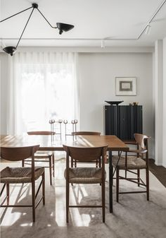 Functionalist villa in Stockholm featured in Residence Magazine: Teak and seagrass dining chairs by Peter Hvidt (Denmark, c.1960s), Svenskt Tenn cabinet model no.2192 by Josef Frank (1954) and a tripod ceiling lamp by Serge Mouille (originally...
