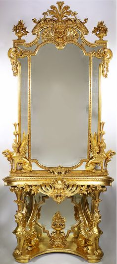 """A Fine French Empire Revival 19th Century Gilt Wood and Gesso Carved Figural Console Table with Matching Mirror. The """"D"""" shaped top console raised by a pair of seated winged sphinxes with notched corner frame over a conforming frieze, centered by a pierced carved Satyr mask with foliate swags, above a mirrored trefoil backboard centered by a flowering urn adorned by chimera, raised on a shaped base and fitted with a Verde d'alps marble top. The figural mirror flanked by a pair o..."""