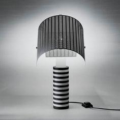 Lampe à poser composée d'un piétement cylindrique en métal vernis noir et blanc et d'un diffuseur orientable réalisé en tôle d'acier perforée et cintrée.Pièce iconique de la maison Artemide,...