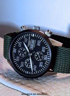 A Maurice de Mauriac Chronograph Modern featuring a 42mm titanium case, black bezel and dial, applied brushed numerals. Powered by an integrated automatic chronograph movement with day & date. Clad on a green Maurice de Mauriac Perlon strap. http://mauricedemauriac.ch/ swiss watches, watches for men, wrist watch
