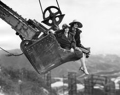 1927. Two women are suspended high above the Hollywoodland sign as they ride on the shovel from Western Construction Co.'s working steam shovel.