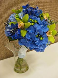 """Something Blue"" Bouquet:  Blue hydrangeas, blue delphinium, green cymbidium orchids, green hypericum berries, wrapped in a blue silk fabric handle trimmed with lace."