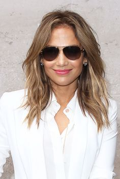 Spotted in London for BBC Radio One, Jennifer Lopez wore her hair in perfect beach waves. She accented her Summer beauty look with aviator sunglasses and a glossy pink lipstick.    I want to find out this shade of color