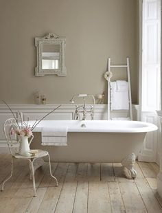 Cream and beige bathroom with warm wooden floor - would love to soak in this tub