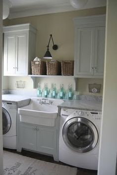 front loading washer and dryer with a sink in the middle. and look at the organization of the baskets!