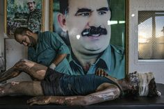 A doctor rubs ointment on the burns of Jacob, a 16-year-old Islamic State fighter, in front of a poster of Abdullah Ocalan, the jailed leader of the Kurdistan Workers' Party, at a Y.P.G. hospital compound on the outskirts of Hasaka, Syria.