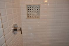 beveled white subway tiles in a straight set pattern with niche