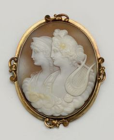 A Victorian shell cameo brooch  Carved to depict the profiles of Hera and Apollo depicted with his lyre, in yellow metal setting, width 4.8cm, length 5.8cm