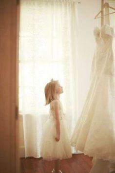 Gorgeous photo of flower girl admiring wedding dress