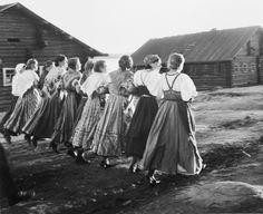 Mustavalkoinen valokuva, jossa ryhmä pitkähameisia naisia tanssii rivissä käsikynkässä.Kuva: Erkki Viitasalo (1942) - Finland
