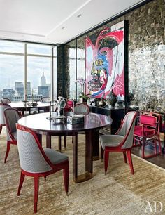 A Basquiat painting strikingly overlays mica paneling in the dining room which features two vintage tables | archdigest.com