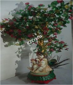 This elegant tree with Lord Krishna bring prosperity and blessing to your home and life. This tree is made up of golden wires having vivid pink and yellow flowers and bright green leaves. INR 2995 only.