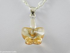 Close up view of the Swarovski crystal butterfly pendant.  The colour is called Golden Shadow and has a backing that brings out even more sparkle.  It is fitted to a silver plated bail and chain.