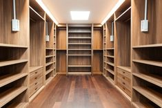 An impressive walk in wardrobe Interior of a modern contemporary house. The timber joinery shelves and cupboards and a timber floor exude quality